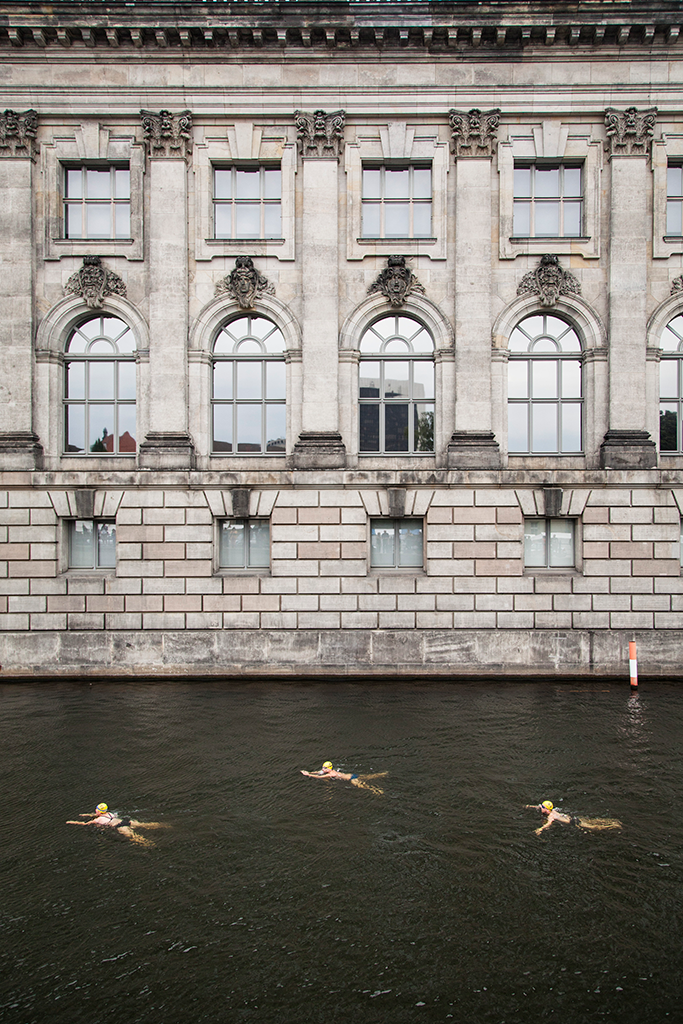 © 2015 Annette Hauschild/Ostkreuz for Flussbad Berlin e.V. First Flussbad Pokal swimming competition (2015) - three swimmers in front of the backdrop of Pergamon Museum.