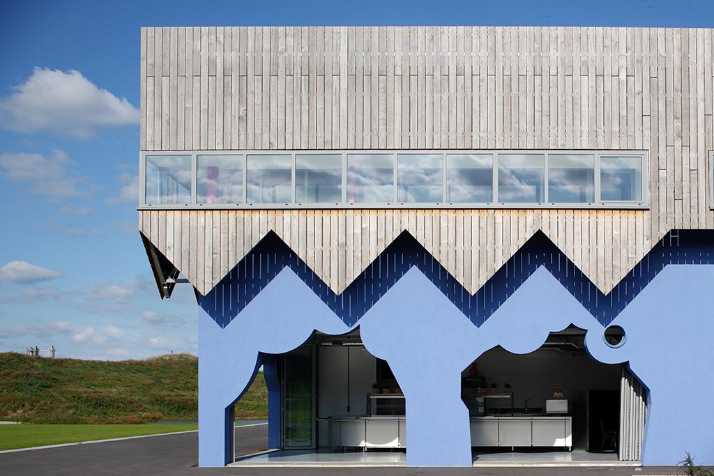 Le bâtiment abrite une salle polyvalente, des bureaux et un café. Ce « hangar décoré» est revêtu d'une enveloppe figurative en bois dont la découpe évoque le passé industriel du site. © Rob Parrish